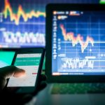 Trading, computers screens with charts and phone